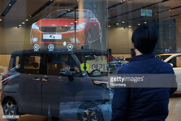 A man looks at an image of a Kia Motors Corp Cerato Forte K3 sedan presented as a 3D hologram projected onto a window at a Kia dealership in Seoul...