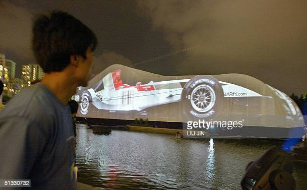 A man looks at an image of BAR Honda race car projected onto a big screen at a Formula One promotion event in Shanghai late 20 September 2004 It is a...