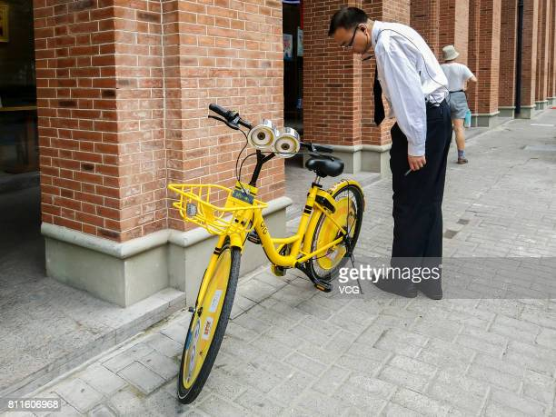 A man looks at an Ofo sharing bike with the version of Minions at the Bund on July 10 2017 in Shanghai China The Ofo one of the leading bike sharing...