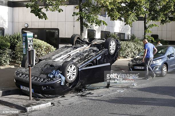 A man looks at an overturned car allegedly used by an UberPOP driver at Porte Maillot in Paris on June 25 as taxi drivers demonstrated nearby...