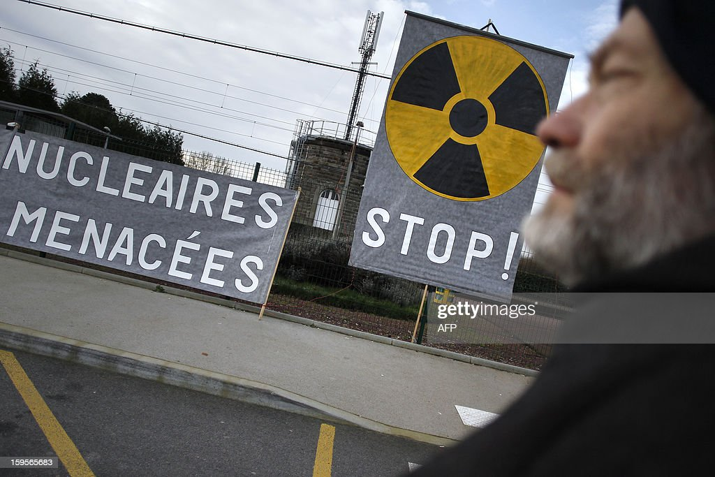 A man looks at anti-nuclear boards hung at the irons of the railway station as a rail convoy carrying highly radioactive spent nuclear waste from Italy to the retreatment factory of La Hague arrives at the French energy giant Areva retreatment factory of Valognes, northwestern France on January 16, 2013. The banner at left partially reads : 'Nuclear waste, threat on health and life'.