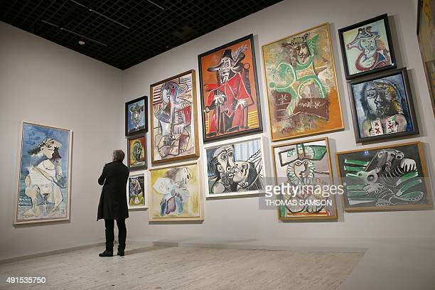 CAPTION A man looks at artworks during the 'PicassoMania' exhibition on October 6 2015 at the Grand palais in Paris The exhibition takes place from...