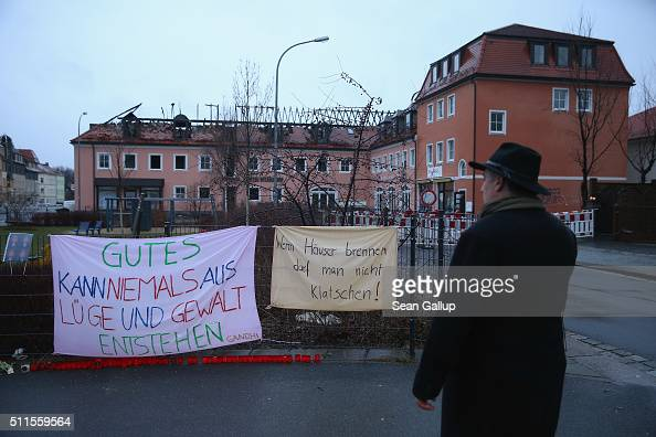 A man looks at banners left by people opposed to the attack next to the burntout remains of a former hotel that was to soon serve as a shelter for...