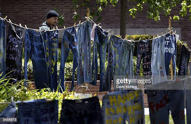 A man looks at blue jeans with messages challenging misconceptions about sexual violence hung by the UCLA Clothesline Project on the University of...