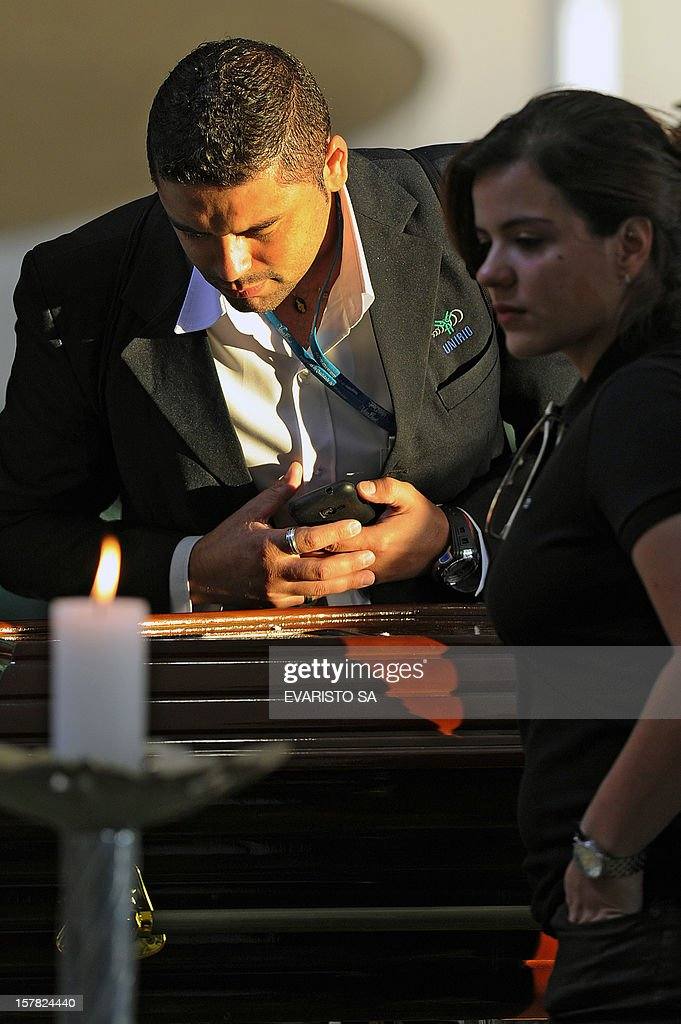 A man looks at Brazilian architect Oscar Niemeyer's coffin during his fineral at Planalto Palace in Brasilia, on December 6, 2012. Niemeyer, the Brazilian icon who revolutionized modern architecture and designed much of the country's futuristic capital Brasilia, died in Rio de Janeiro Wednesday at 104. The body will return to Rio for another funeral wake followed by the burial, according to Rio de Janeiro's Mayor Eduardo Paes. AFP PHOTO / Evaristo SA