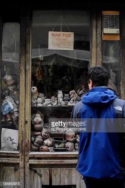 A man looks at broken dolls displayed in the shop window of the restorer shop 'Restauri Artistici Squatriti' on December 2 2011 in Rome Local...
