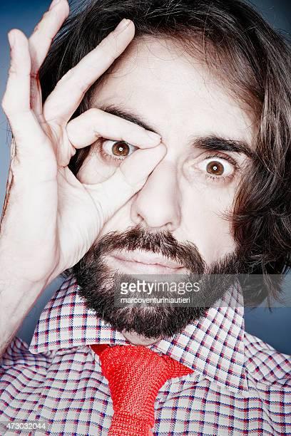 Man looks at camera while circling his eye with hand