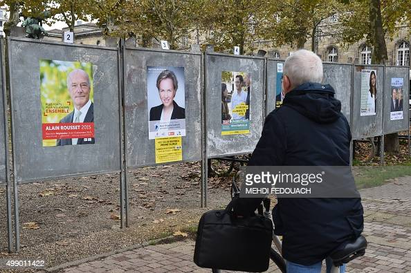 A man looks at campaign posters on November 28 2015 in Bordeaux ahead of the December 613 regional elections in the AquitaineLimousinPoitouCharentes...