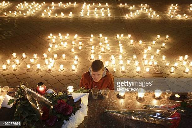 A man looks at candles and flowers in Simferopol on November 1 2015 in memory of the victims of a jetliner crash Russia mourned its biggest ever air...