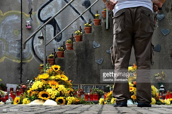A man looks at candles and flowers left by mourners at the makeshift memorial to victims of the Love Parade disaster on its fifth anniversary on July...