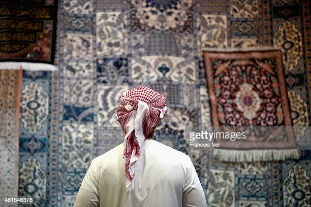 A man looks at carpets on display at Central Souq on July 22 2015 in Sharjah United Arab Emirates