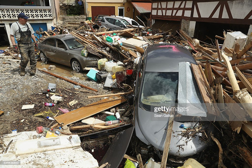 A man looks at cars smashed among debris following a furious flash flood the night before on May 30, 2016 in Braunsbach, Germany. The flood tore through Braunsbach, crushing cars, ripping corners of houses and flooding homes during a storm that hit southwestern Germany. Miraculously no one in Braunsbach was killed, though three people died as a result of the storm in other parts of the country.