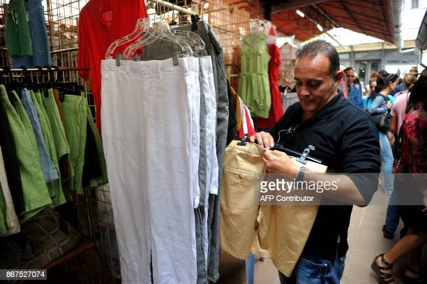 A man looks at clothes at a market in Havana on October 27 2017 Almost drowned by the crisis of the 90s the emerging Cuban fashion begins to thrive...