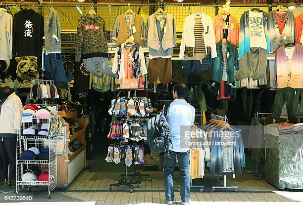 A man looks at clothes in front of a clothing store at Ameyoko market in Tokyo Japan Sep 2013 Ameyoko is a bustling outdoor marketplace and Tokyo's...