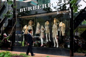 A man looks at clothes on display in the window of Burberry's new flagship store on April 25 2014 in Shanghai China