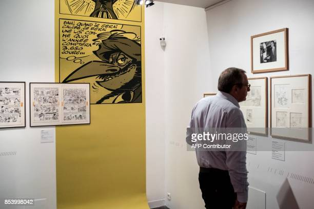 A man looks at comic strips displayed during a preview of an exhibition dedicated to the work of French comics editor and scriptwriter Rene Goscinny...