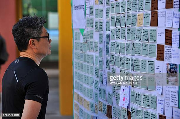 A man looks at condolence messages posted on a board in memory of the victims from an earthquake on Malaysia's Mount Kinabalu at the Tanjong Katong...