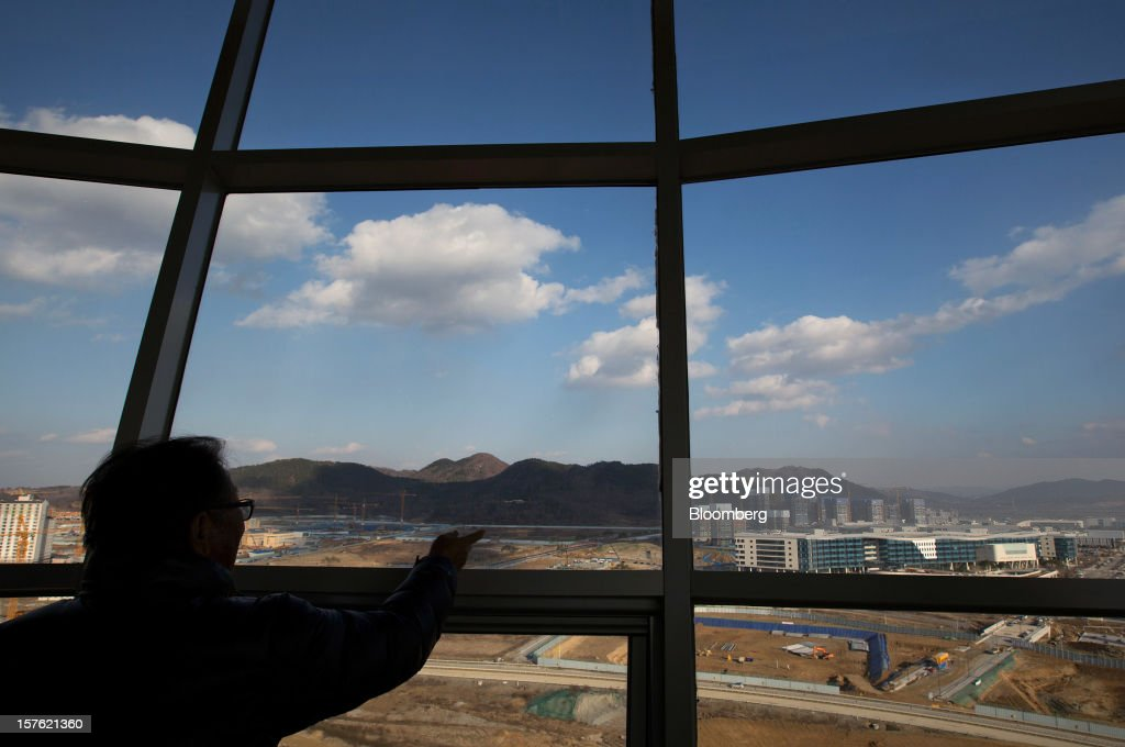 A man looks at construction sites from an observation deck in Sejong, South Korea, on Tuesday, Dec. 4, 2012. The construction of Sejong City 120 kilometers (75 miles) south of the capital fulfills the vision of the late President Roh Moo Hyun, who pledged to reduce the dominance of Seoul and pump money into a region courted for its swing voters. Photographer: SeongJoon Cho/Bloomberg via Getty Images