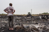 A man looks at debris from an Malaysia Airlines plane crash on July 18 2014 in Grabovka Ukraine Malaysia Airlines flight MH17 travelling from...