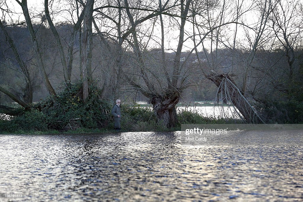 A man looks at flooded fields and roads close to the village of North Curry on November 21, 2012 near Taunton, England. Heavy rain overnight has brought widespread disruption to many parts of the UK particularly in the Somerset and Wiltshire and weather forecasters have warned of more wet and windy weather to come.