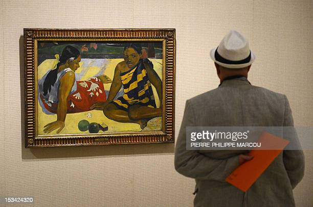 A man looks at French artist Paul Gauguin's painting 'Parau Api What's new' at the Thyssen Bornemisza museum in Madrid on October 5 2012 The...