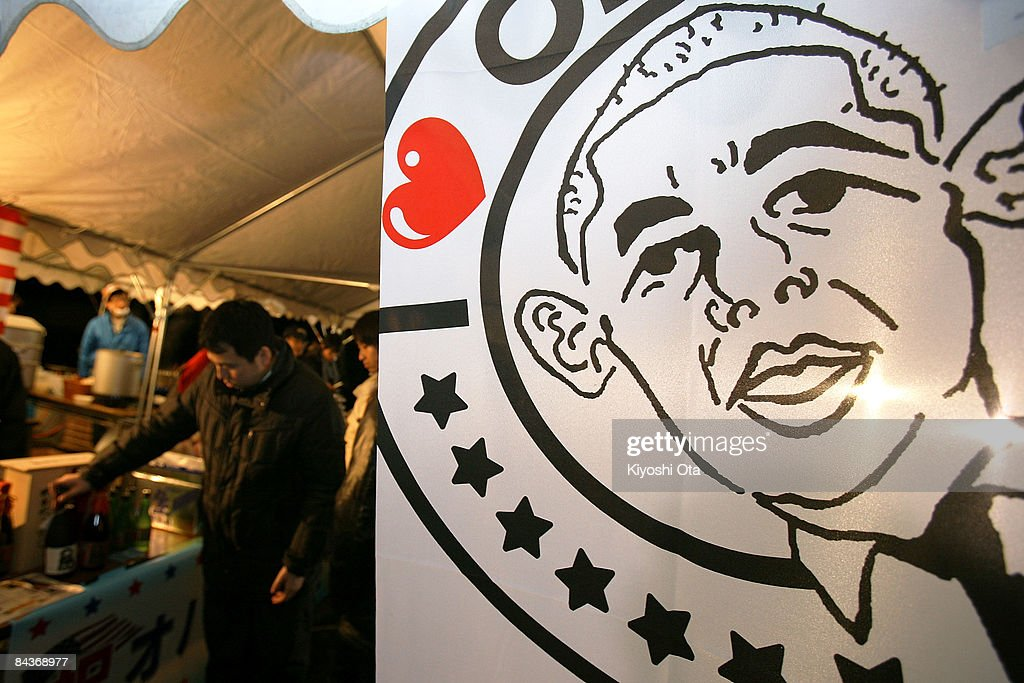 A man looks at goods in support of US Presidentelect Barack Obama behind a 'I Love Obama' banner as people gather to celebrate his inauguration at...