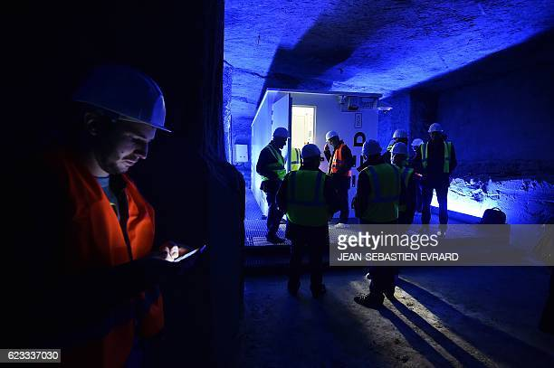 A man looks at his cellphone as people visit a room of cabling servers in an underground datacenter on November 15 2016 near Saumur western France...