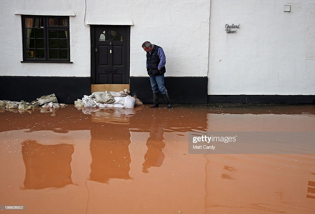 A man looks at his flooded property in the centre of the village of Ruishton, near Taunton, on November 25, 2012 in Somerset, England. Another band of heavy rain and wind continued to bring disruption to many parts of the country today particularly in the south west which was already suffering from flooding earlier in the week.