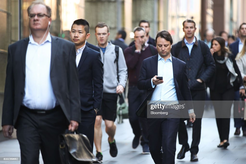 A man looks at his mobile phone as he and other commuters walk through Martin Place in Sydney, Australia, on Thursday, Aug. 17, 2017. Australian employers added more jobs than forecast in July, underscoring the central banks confidence in an improving labor market. Photographer: Brendon Thorne/Bloomberg via Getty Images