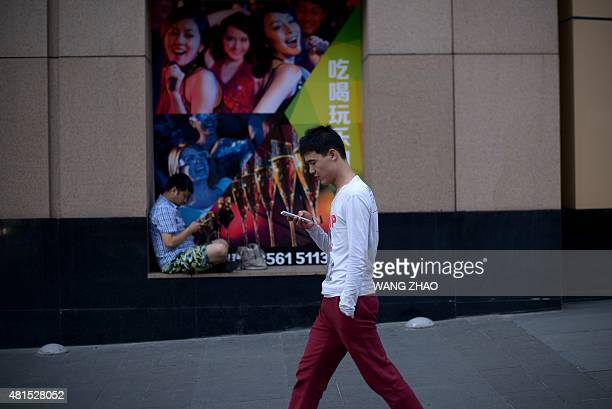 A man looks at his mobile phone as he walks past a poster at the entrance of a mall in Beijing on July 22 2015 AFP PHOTO / WANG ZHAO
