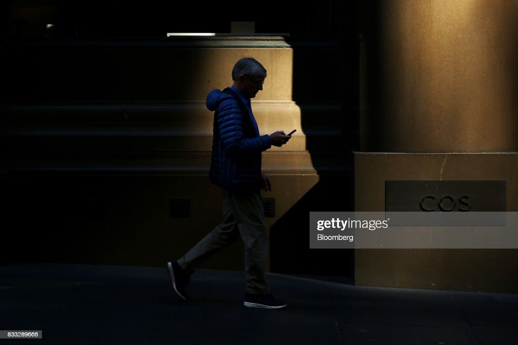 A man looks at his mobile phone as he walks through Martin Place in Sydney, Australia, on Thursday, Aug. 17, 2017. Australian employers added more jobs than forecast in July, underscoring the central banks confidence in an improving labor market. Photographer: Brendon Thorne/Bloomberg via Getty Images