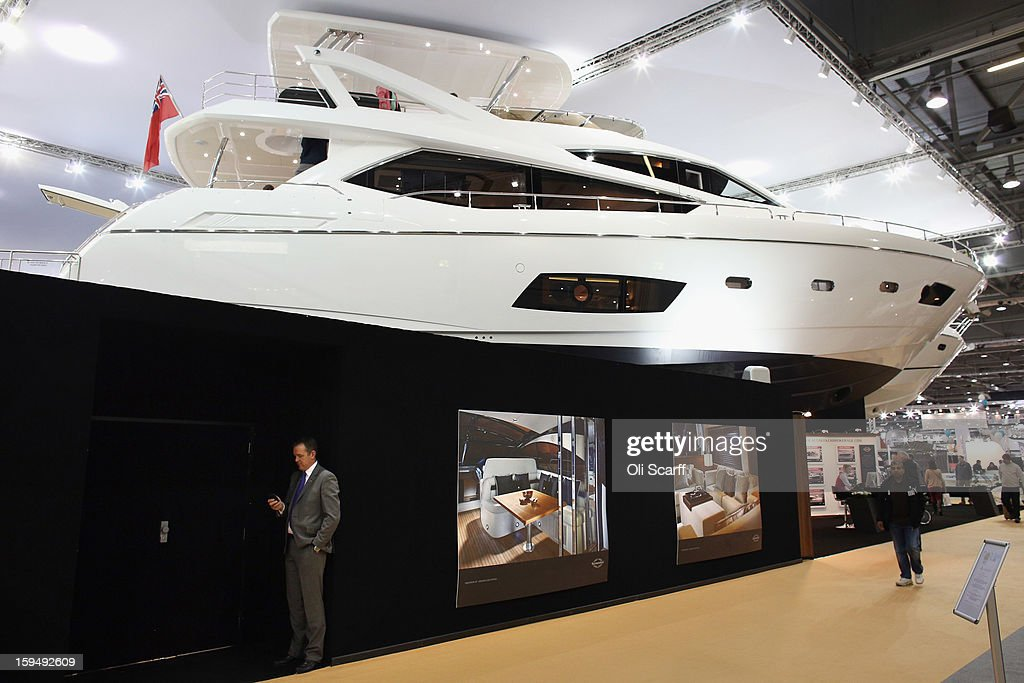 A man looks at his mobile phone beneath a powerboat on the Sunseeker stand at the 2013 London Boat Show, held at the ExCeL Centre, on January 14, 2013 in London, England. Until January 20, 2013 the London Boat Show will showcase, demonstrate and sell maritime equipment ranging from luxury yachts to dinghies.