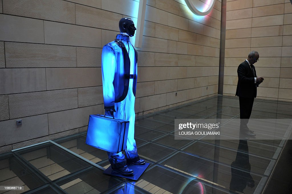 A man looks at his mobile phone by a sculpture of a banker at the National Bank of Greece premises on November 14, 2012.