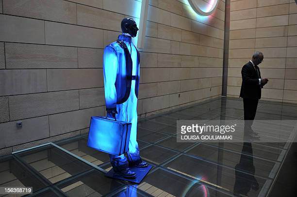 A man looks at his mobile phone by a sculpture of a banker at the National Bank of Greece premises on November 14 2012 AFP PHOTO / LOUISA GOULIAMAKI