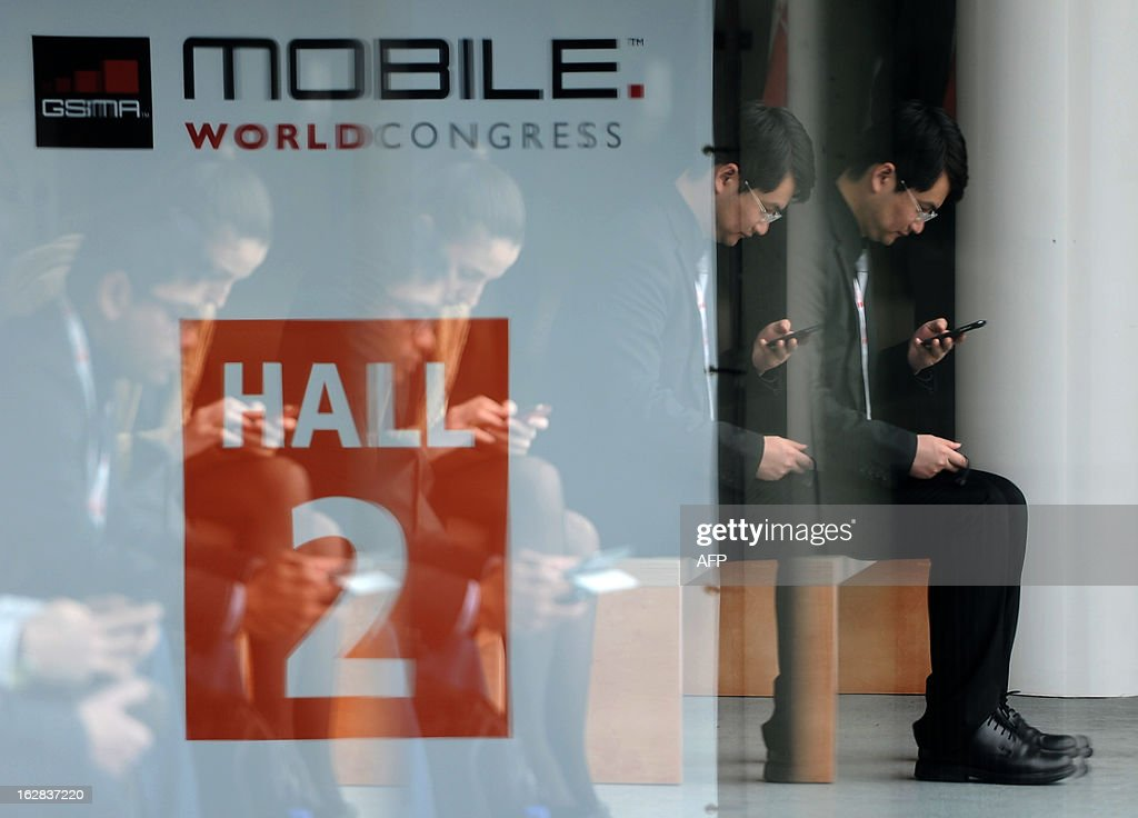 A man looks at his mobile phone during the 2013 Mobile World Congress in Barcelona on February 28, 2013. The 2013 Mobile World Congress, the world's biggest mobile fair, is held from February 25 to 28 in Barcelona. AFP PHOTO / LLUIS GENE.