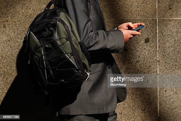 A man looks at his mobile phone while walking through the central business district in Sydney Australia on Thursday Aug 13 2015 Australian business...