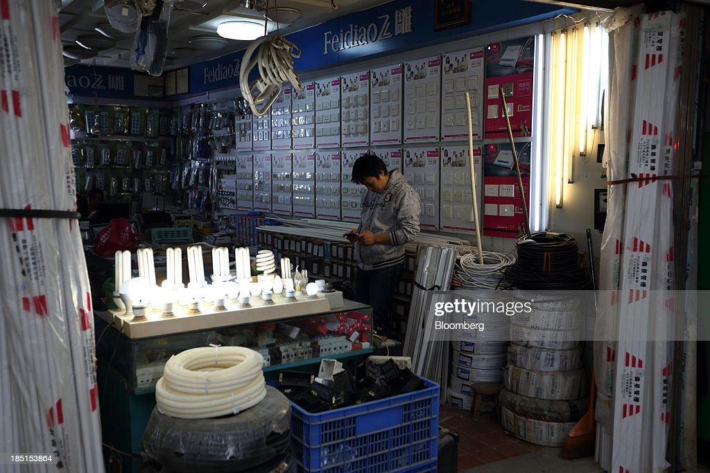 A man looks at his smartphone as he stands next to a display of fluorescent light bulbs at a store in Wuhan, China, on Thursday, Oct. 17, 2013. China is scheduled to release third-quarter gross domestic product figures on Oct. 18. Photographer: Tomohiro Ohsumi/Bloomberg via Getty Images
