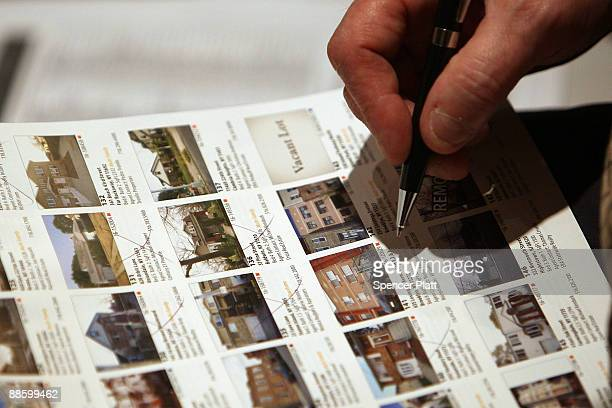 A man looks at homes to be auctioned at an auction for more than 25 foreclosed homes by auctioneers at Hudson Marshall at the Renaissance Newark...