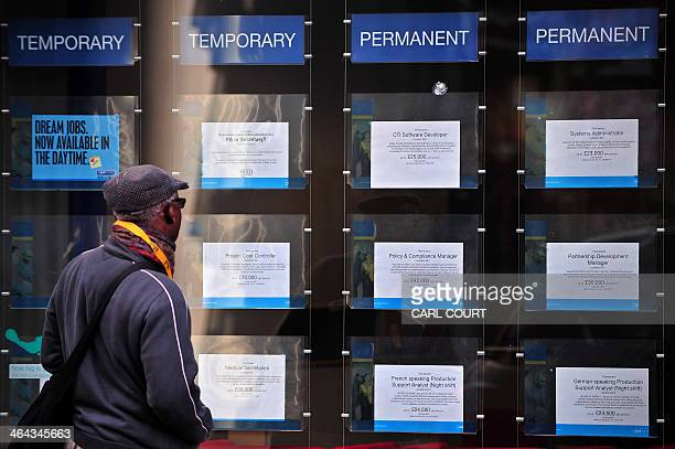 A man looks at job adverts in the window of a job recruitment centre in central London on January 22 2014 Britain's economic recovery won further...