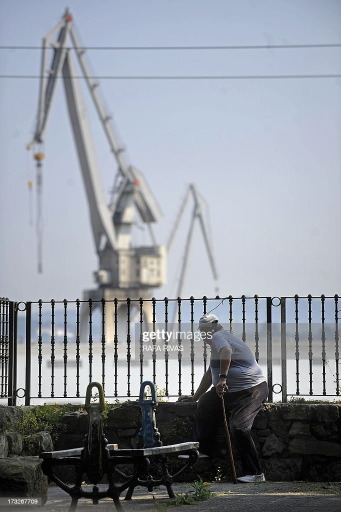 A man looks at La Naval shipyard during a protest against the repayment of state aids by Spanish shipbuilders in the Northern Spanish Basque village of Sestao, on July 11, 2013. Brussels will decide by July 17 if the roughly three billion euros (4.0 billion USD) in state aid which Spanish shipbuilders received between 2005 and 2011 were unauthorised and if they will have to pay the money back. Unions have called for a day of protest and strikes on July 11 when European Union's commissioner for competition, Joaquin Almunia, will meet with representatives of Spanish shipbuilders in Brussels.