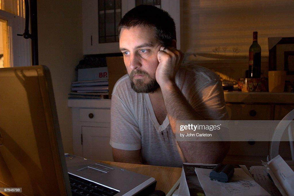 Man looks at laptop : Stock Photo