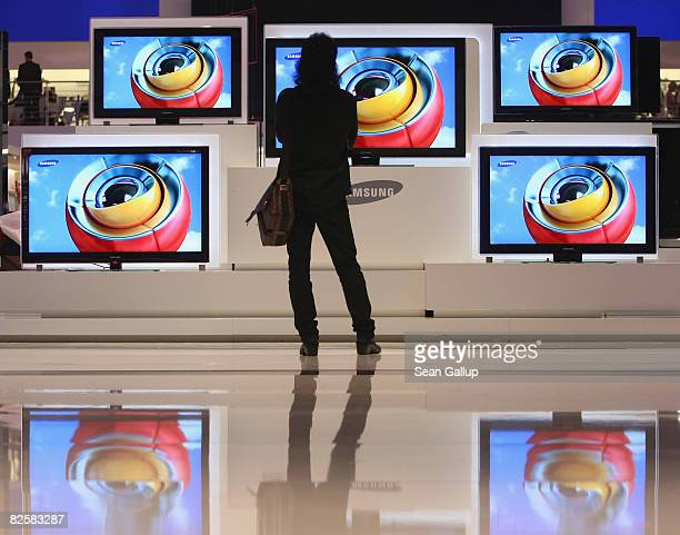 A man looks at large screen flat panel LCD television monitors at the Samsung stand ahead of the opening evening at the IFA consumer elctronics trade...