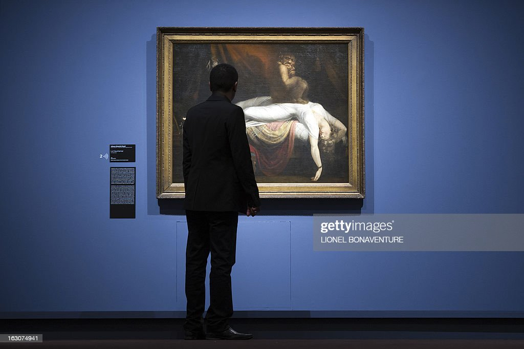 A man looks at 'Le Cauchemar' (The Nightmare) painting by Johann Heinrich Fussli displayed during the exhibition 'The Angel of the Odd. Dark Romanticism from Goya to Max Ernst' at the Orsay museum in Paris, on March 4, 2013. The exhibition will run from March 5 until June 9, 2013.