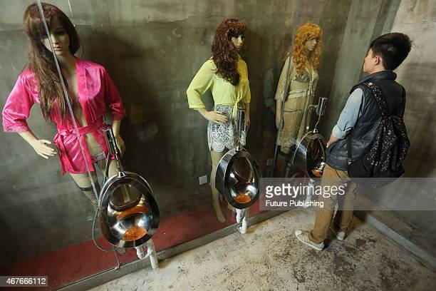 A man looks at mannequins dressed in skimpy lingerie placed behind the glass wall of a urinal in a restaurant in Taiyuan on March 25 2015 in Shanxi...