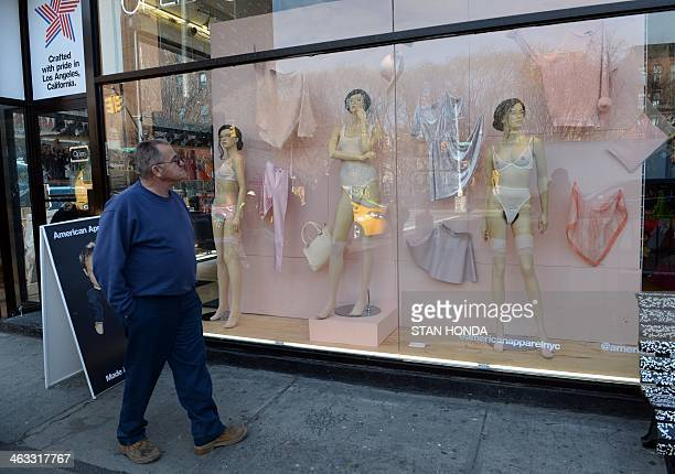 A man looks at mannequins with pubic hair in the window of an American Apparel shop on Houston Street in the Soho section of Manhattan January 17...