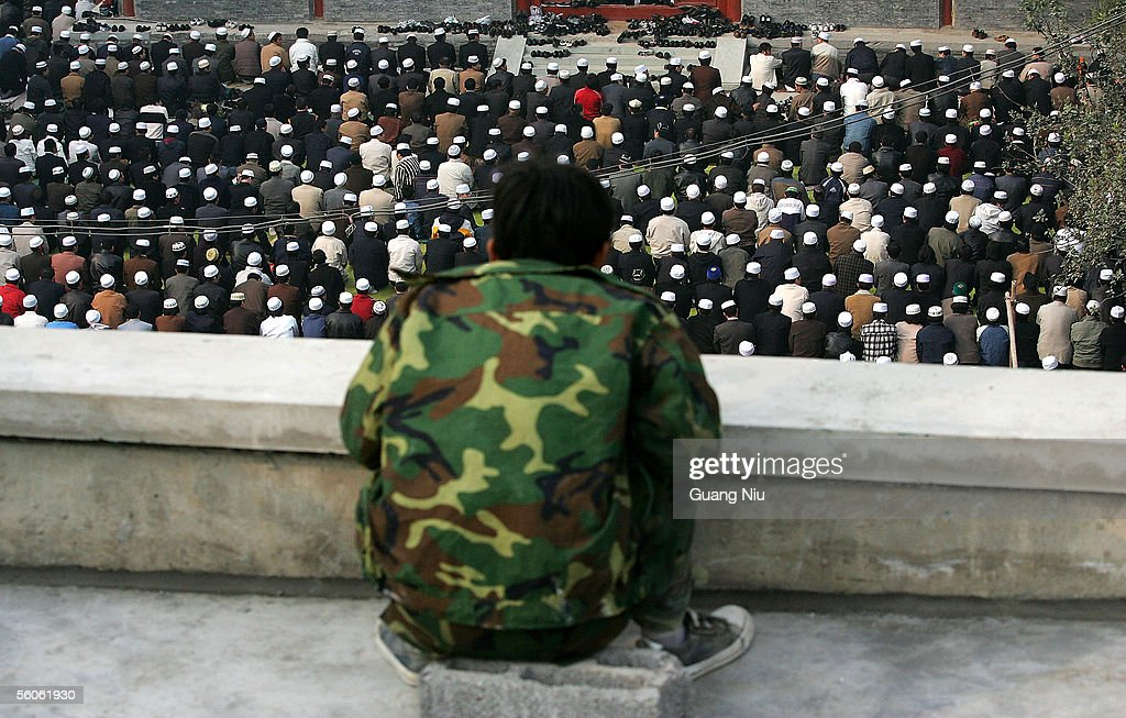 A man looks at Muslims praying to mark the Festival of Fast-Breaking after the Ramadan month in the Niujie Mosque on November 3, 2005 in Beijing, China. The Niujie Mosque is the largest mosque in China's capital and dates back to the 10th century and has been closed for the past six months for renovations and expansion.