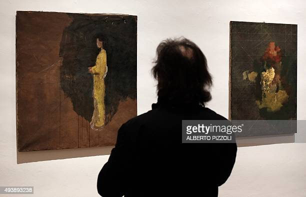 A man looks at paintings by late French artist Balthus as he visits the exhibition dedicated to his work at the Villa Medici in Rome on October 23...