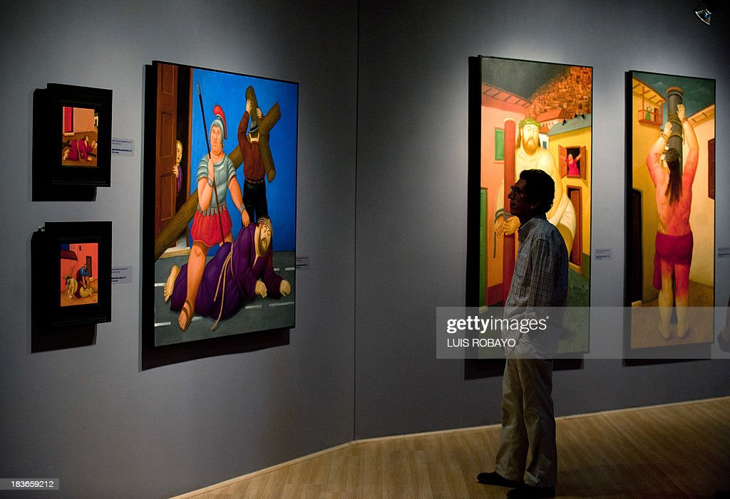 A man looks at paintings of the exhibition 'Via Crucis, the passion of Christ' of Colombian artist Fernando Botero, on October 8, 2013, in Cali, department of Valle del Cauca, Colombia. Botero was the curator of his own exhibition, which is composed of 27 oil paintings and 34 drawings combining traditional aspects of Catholicism and the modern world.