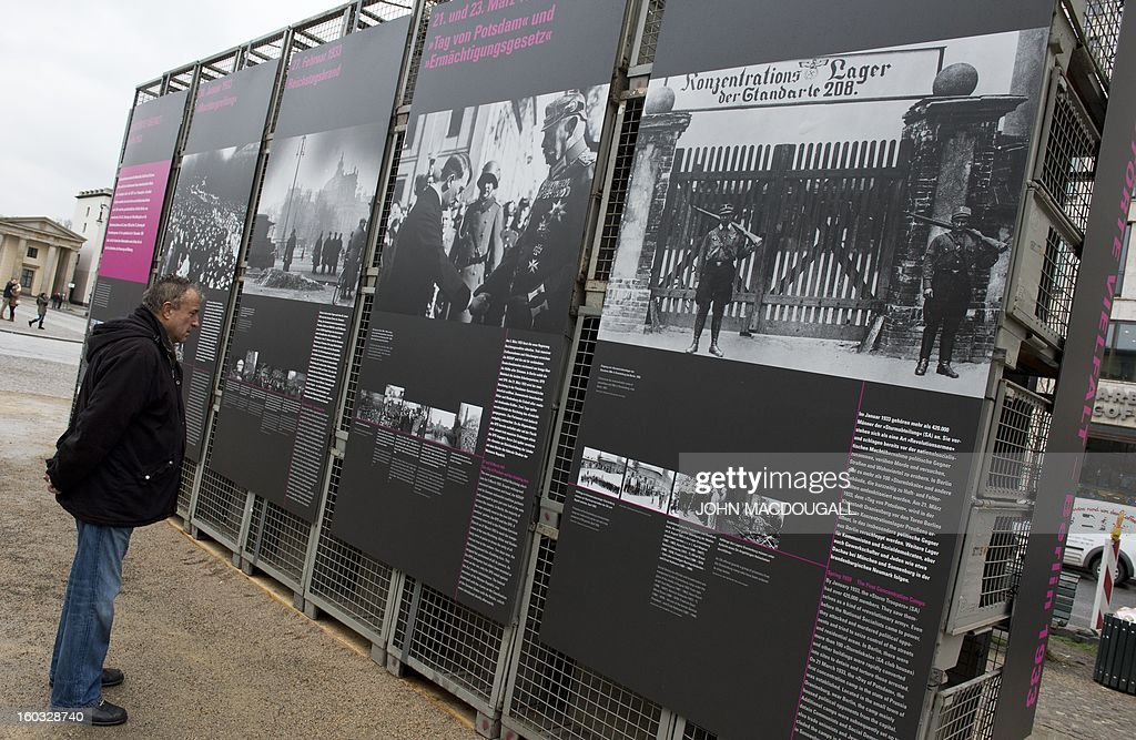 A man looks at panels detailing the Nazi's rise to power near Berlin's Brandenburg Gate January 29, 2013, to coincide with the 80th anniversary of Adolf Hitler's accession to power January 30, 1933.