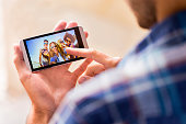 Man Looks At Photo Of Friends On Smartphone
